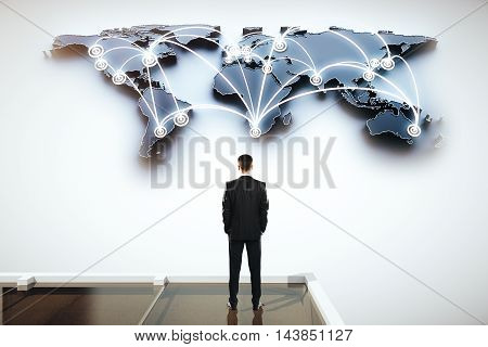 Global social networking concept with businessman looking at abstract map with network on light grey background