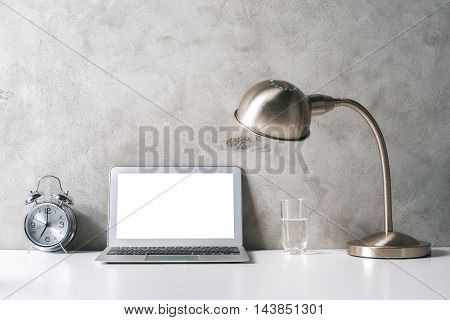 Closeup of creative designer workplace with blank white laptop alarm clock glass of water and table lamp on concrete wall background. Mock up