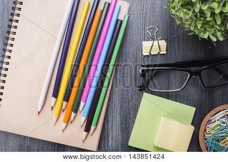 Close up of colorful pencils spiral notepad glasses stickers peg paper clips and decorative plant on wooden desktop. Top view