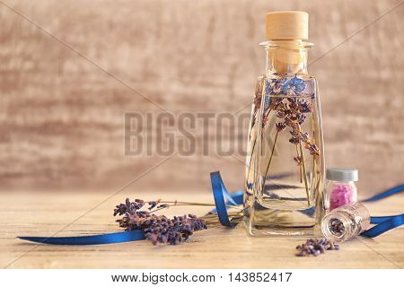 Glass bottle with spa oil and lavender flower, closeup