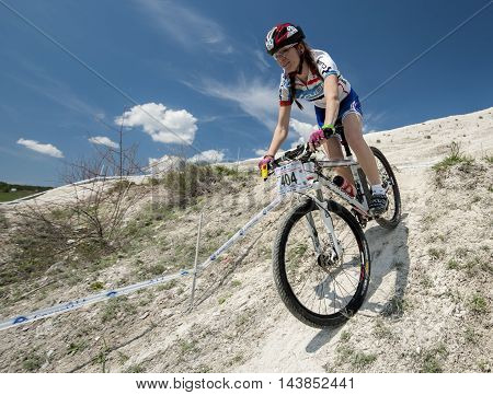 KHVALYNSK - MAY 7, 2016: Female cyclist descends from the slope at XCE eliminator track championship 'Match of Russian cities' on May 7, 2016 in Khvalynsk, Saratov region, Russia.