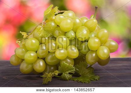 bunch of ripe green grapes on a wooden table with a blurred background