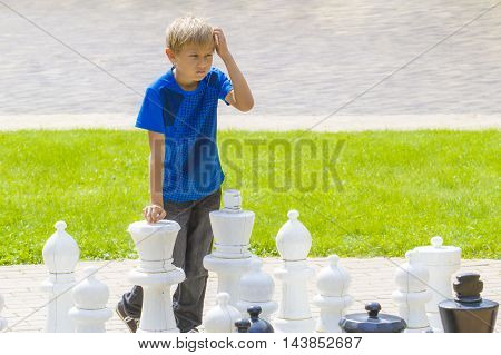 Boy playing giant chess outdoor in park