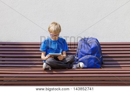 Boy with glasses using tablet PC. Child with backpack sitting on the bench. Free copy space. Education, technology, people concept