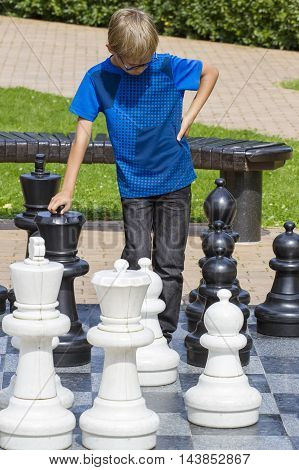 Boy playing giant chess outdoor. Child thinking strategically about his next move