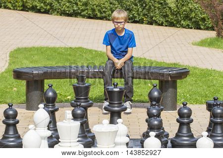 Outdoor chess game using life sized chess pieces and chess board. Concentrated child, thinking about his next move, sitting on a wooden bench.
