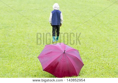 Rainy weather. Sad little boy go away. Red umbrella on the green grass.