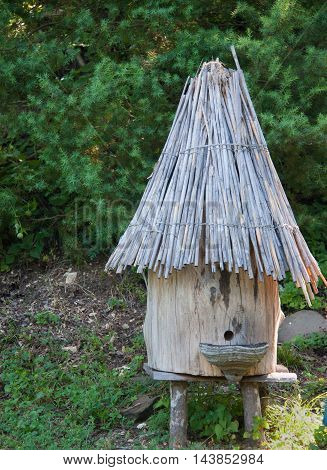 cylindrical wooden beehive with thatched roof in old style.