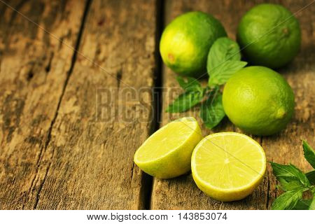 Juicy limes and fresh mint on a wooden background