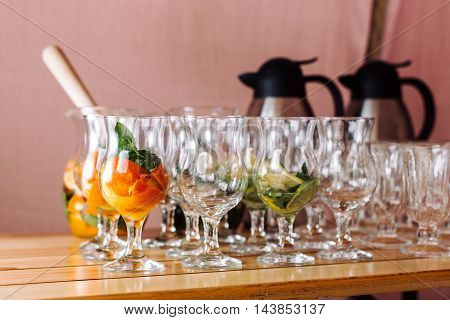Glasses with ingredients for cocktails, mint and orange. A few glasses. Standing on a wooden table, without the liquid only ingredients.