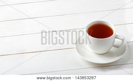 White ceramic cup of tea on a white wooden table. Copyspace. Angle view.