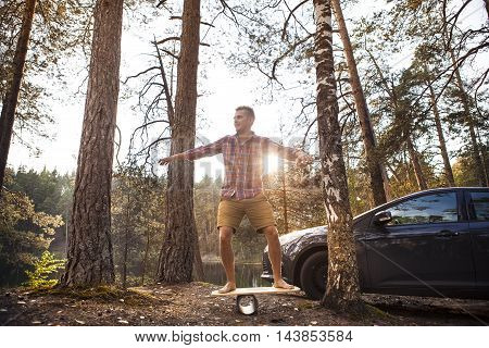 Young man spending time outdoors, on weekend in the forest with his car and balance board