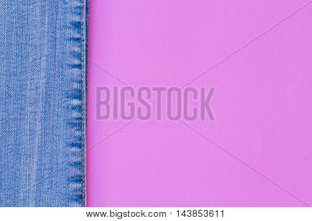 background combination of blue and pink. Top view of blue jeans on a pink background