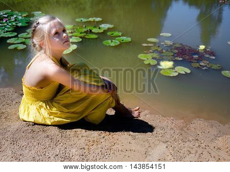 Beautiful girl in yellow sundress sitting by the pond with water lilies