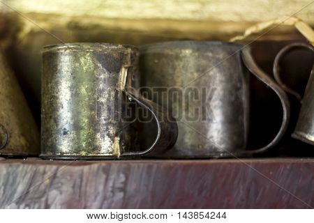 Antique tin cups sit on shelf in wooden cottage.