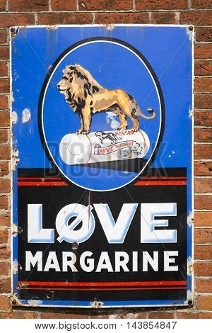VEJLE DENMARK - AUGUST 22 2016: Danish vintage metal Lion Margarine signboard at a wall with old bricks on August 22 2016