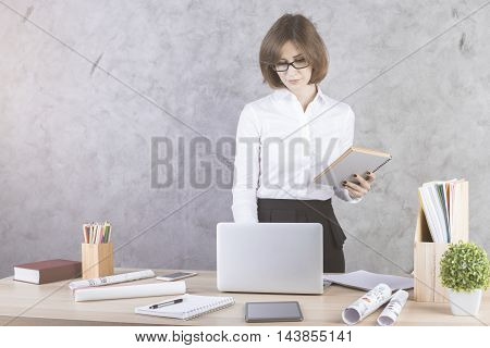 Woman With Paperwork Using Laptop
