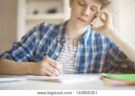 Young man doing his assignment while talking on mobile phone at office desk. Closeup Blurry background