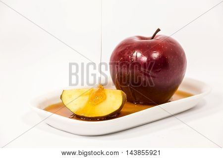 Pouring Honey On Red Apple And Red Apple Slice On White Plate With Honey Isolated On A White Backgro
