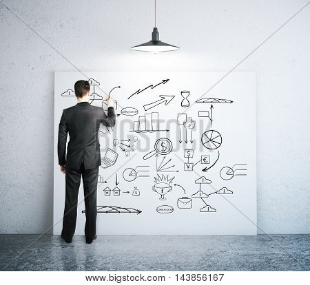 Businessman drawing business sketch on whiteboard in leaning on wall in concrete room