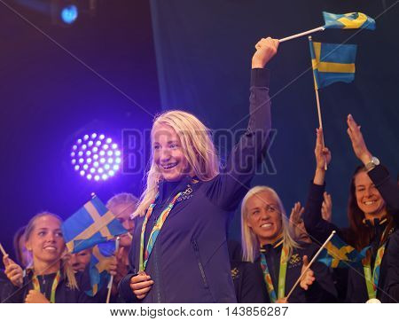 STOCKHOLM SWEDEN - AUG 21 2016: Happy swedish female wrestler Sofia Mattson waiving a flag when swedish olympic athletes are celebrated in Kungstradgarden StockholmSwedenAugust 21 2016
