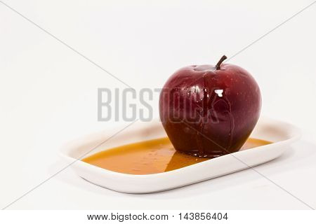 Red Apple With Drops Of Honey On White Plate With Honey Isolated On A White Background