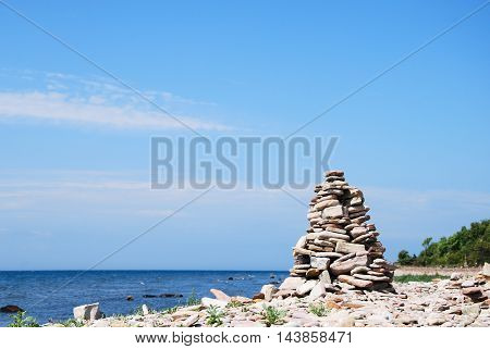 One stone sculpture by the coastline with horizon and blue water in the background