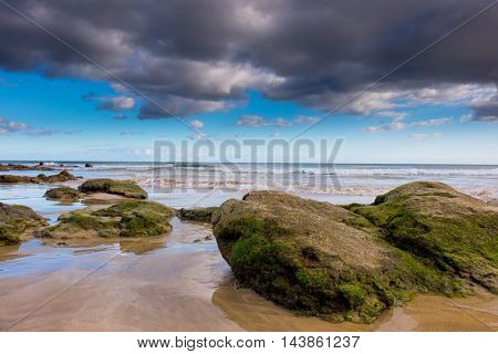 Stones and cloudy sky in sea