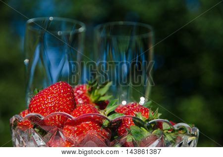 Bowl with fresh strawberries with blurred champagne glasses in the background in a garden