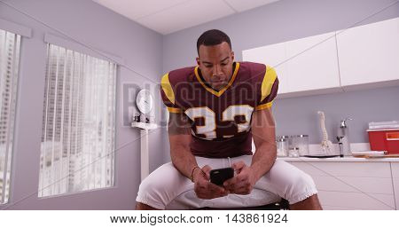 African-american football player texting while waiting in a hospital room.