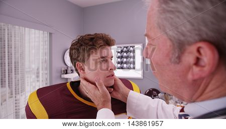 Senior Medical Doctor Examining Sports Athlete's Neck