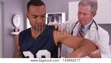 Middle Aged Male Physician Treating Young Male Adult Athlete's Injury