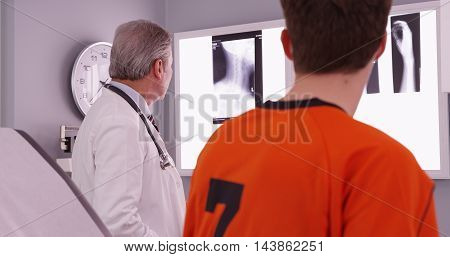 Medical Doctor Reviewing Sports Athlete's Neck Injury Xrays