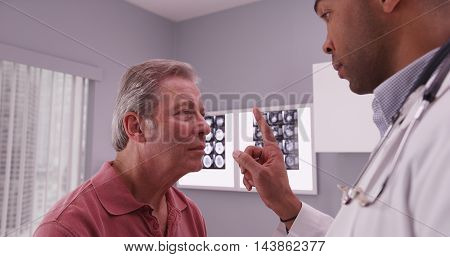African-american Doctor Examining Head Trauma Of Senior Caucasian Patient