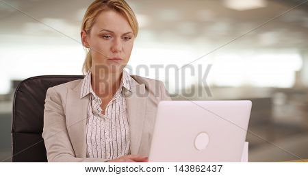 Serious Businesswoman working on laptop at desk