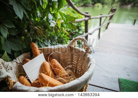 Basket filled with bread against the backdrop of the lake with a bridge. Blank sheet of paper for the label.