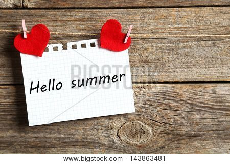 Blank paper hanging on rope on grey wooden background, hello summer