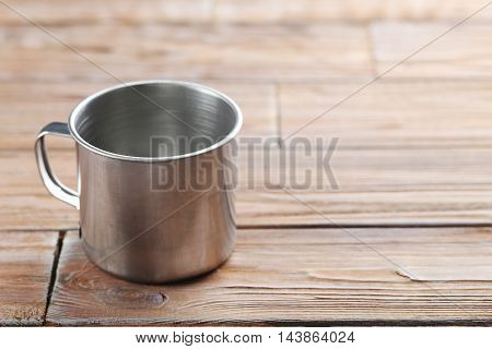 Metal cup on brown wooden table, close up