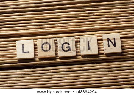 LOGIN word written on wood block at wooden background.