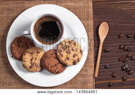 Cup of hot coffee and cookies with chocolate and nuts in plate on brown wooden table top view