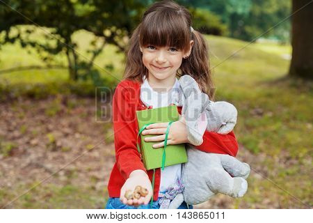 stylish little cute girl with elephant walking in the park