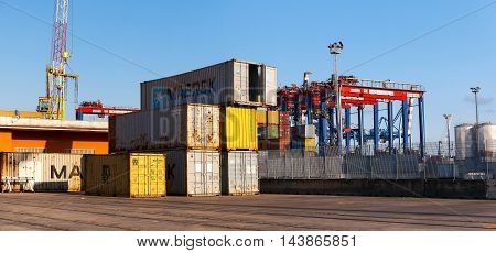 Naples Italy - August 10 2016: In the commercial port city some containers parked waiting for the goods to be distributed. In the background of the special cranes used for handling the heavy loads of goods unloaded from ships.
