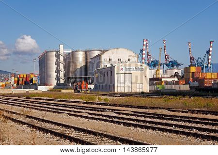 Naples Italy - August 10 2016: In the city's commercial port containers and silos for the transport and storage of goods unloaded from ships. The inner rail and a locomotive used for handling.
