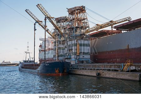 Naples Italy - August 10 2016: Ship docked in the port construction sites is demolished with special cranes.