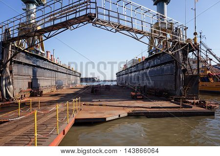Naples Italy - August 10 2016: In the industrial port a special scaffolding in steel with two cranes next door used on site to work on the hulls of boats.
