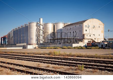 Naples Italy - August 10 2016: In the commercial port city of silos for storage of goods and in the foreground the tracks of the inner rail used for cargo handling.