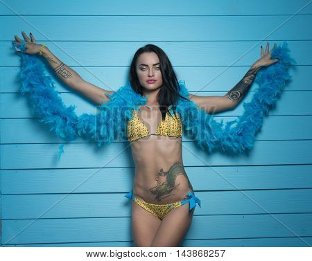 Beautiful seductive brunette woman wearing yellow bikini and blue feather boa looking into the camera and posing over blue wooden wall background
