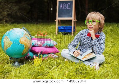smart little boy with glasses writes in a notebook