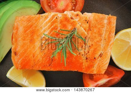 healthy sea food: grilled salmon on iron pan over wooden plate with lemon avocado and tomatoes isolated on white background