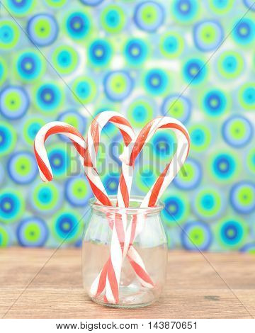 Three candy canes with a colorful background